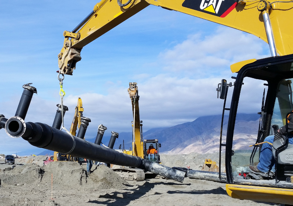 Backhoe lifting piping in mountain range